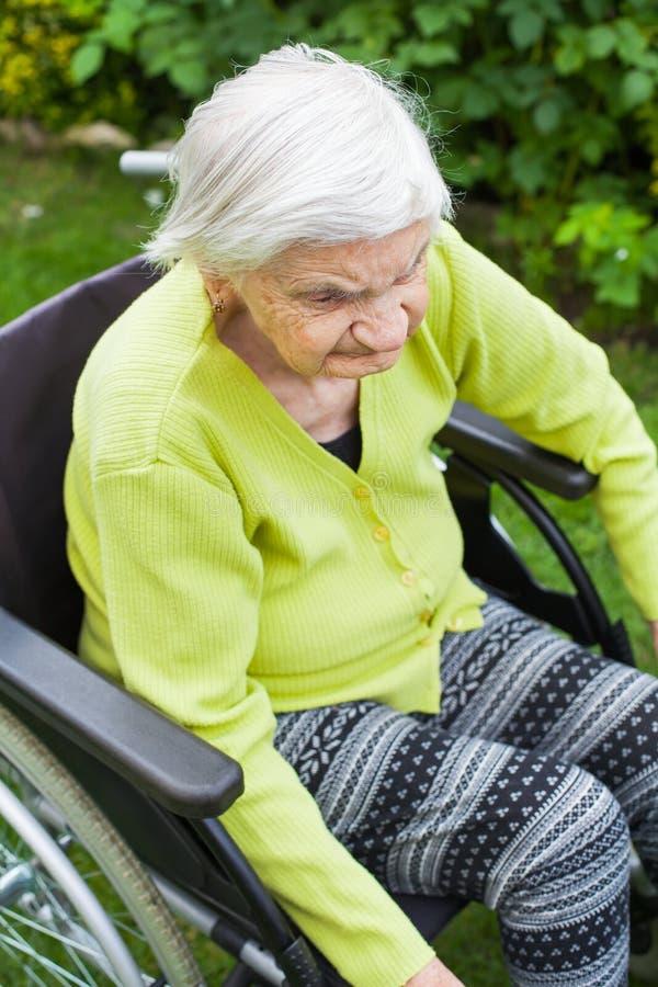 Starej damy obsiadanie w wózku inwalidzkim obrazy royalty free