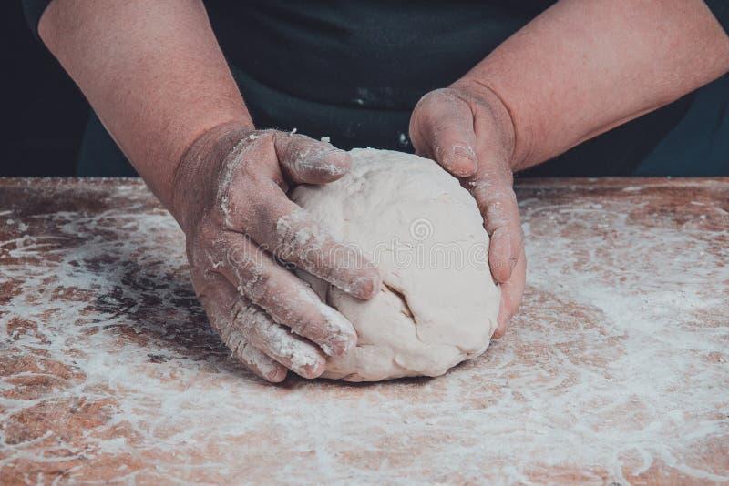 Starej kobiety babcia ugniata ciasto dla kulinarnego chleba zdjęcie royalty free