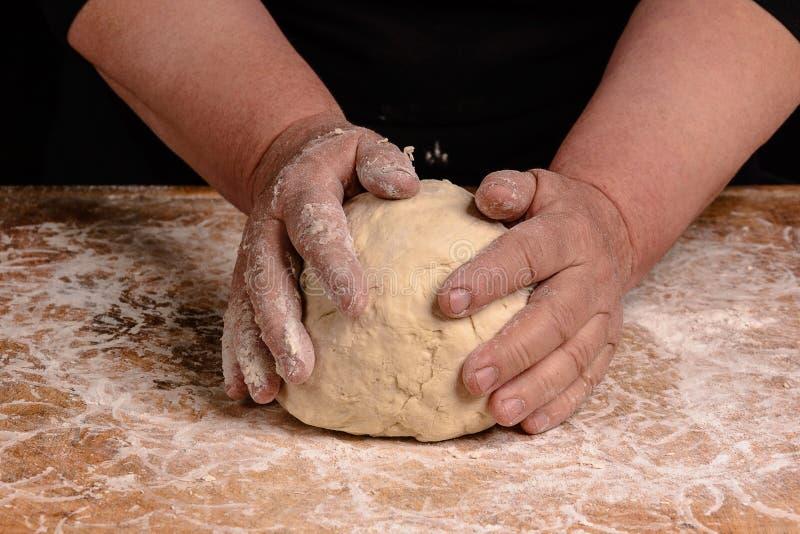 Starej kobiety babcia ugniata ciasto dla kulinarnego chleba zdjęcie stock