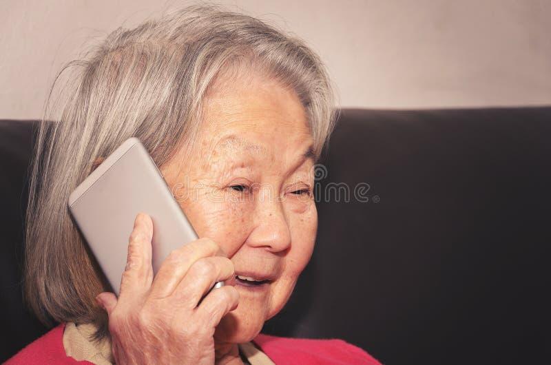 Starej kobiety opowiadać szczęśliwy na telefonie zdjęcia royalty free