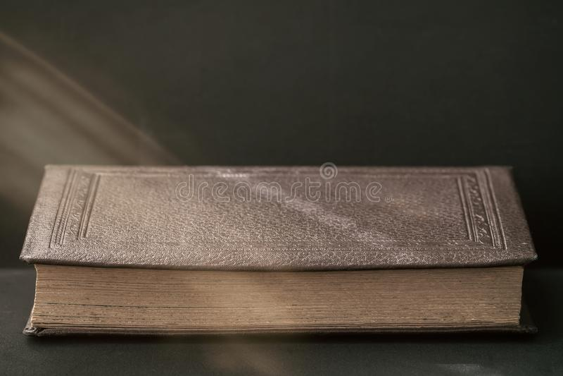 Starej książki zakończenie pod sunbeam na ciemnym tle, kopii przestrzeń, rocznik, nieociosany przełaz Czytelniczy czas szkoła, z  fotografia stock