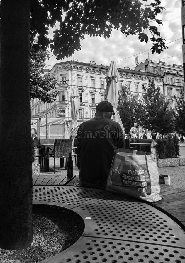Starej osoby obsiadanie przy parkiem fotografia stock