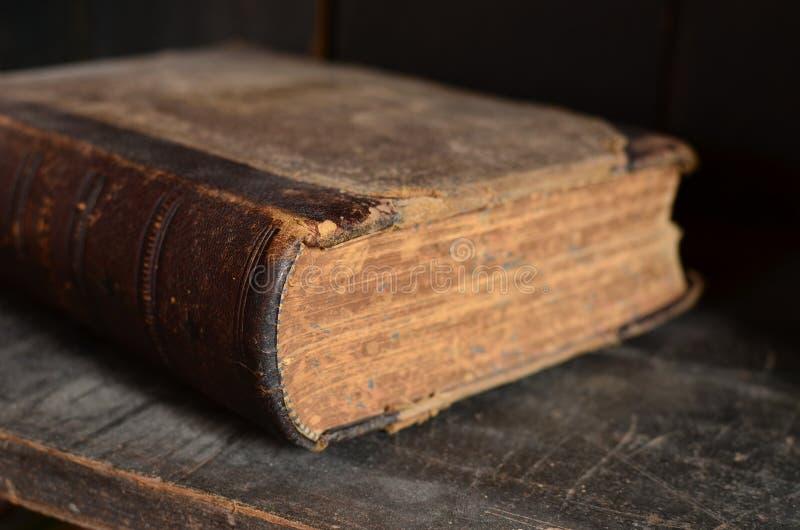 Starej skóry granicy książkowy kłaść na zakurzonym drewnianym półka na książki fotografia royalty free