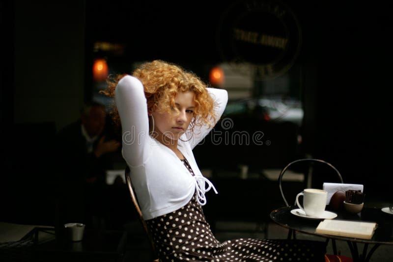 Starende blik van een gelukkige jonge vrouw in een straatkoffie royalty-vrije stock afbeelding