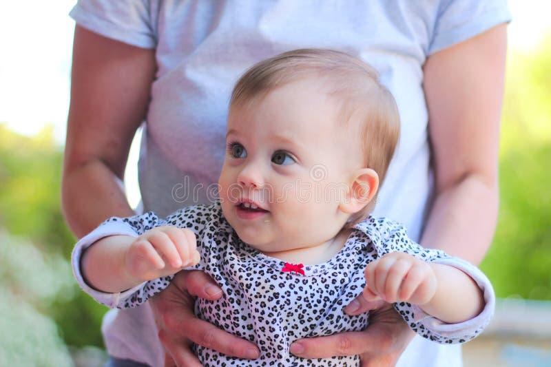 starende blik van het glimlachen weinig kind met blond haar in mom& x27; s handen stock foto's