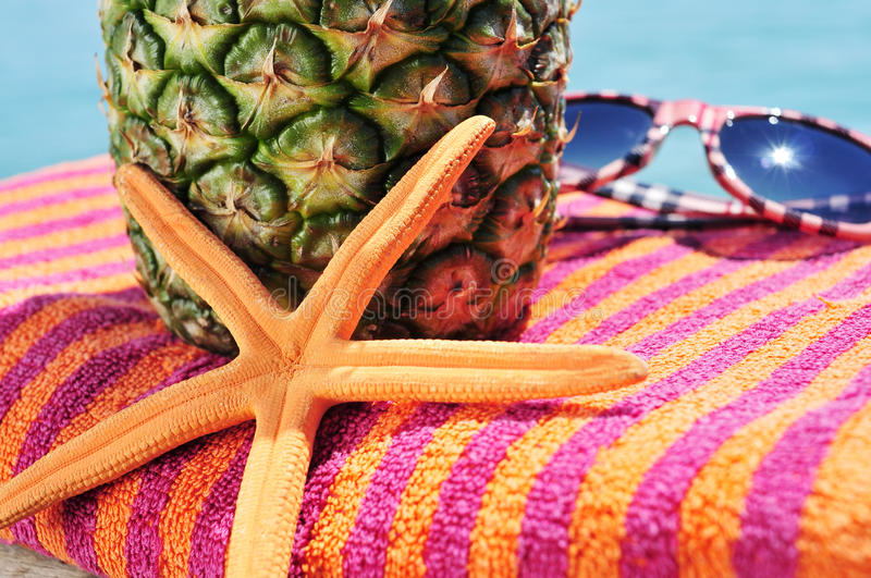 Starfish, beach towel, pineapple and sunglasses. Closeup of a starfish, a pineapple and a pair of sunglasses on a colorful beach towel royalty free stock images