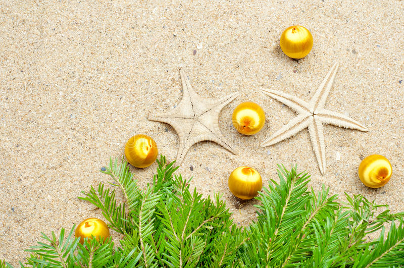 Starfish with Christmas balls and fir tree on the sand stock photos