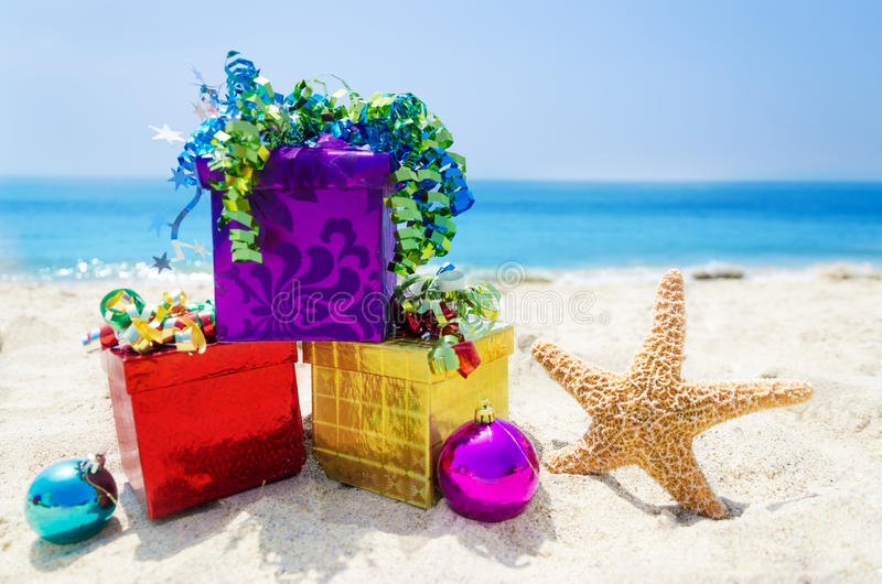 Starfish with Christmas balls and gift on the beach - holiday co