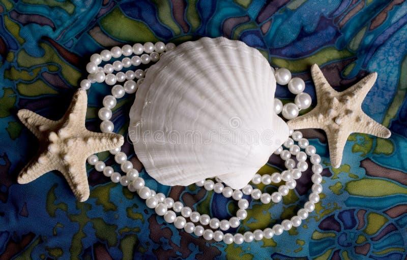 Starfish, Cockleshells und Perlen lizenzfreie stockfotos