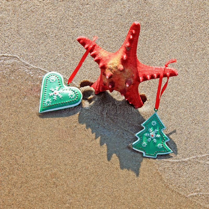 Starfish decorated with christmas toys with shadow as christmas tree on the beach royalty free stock photography