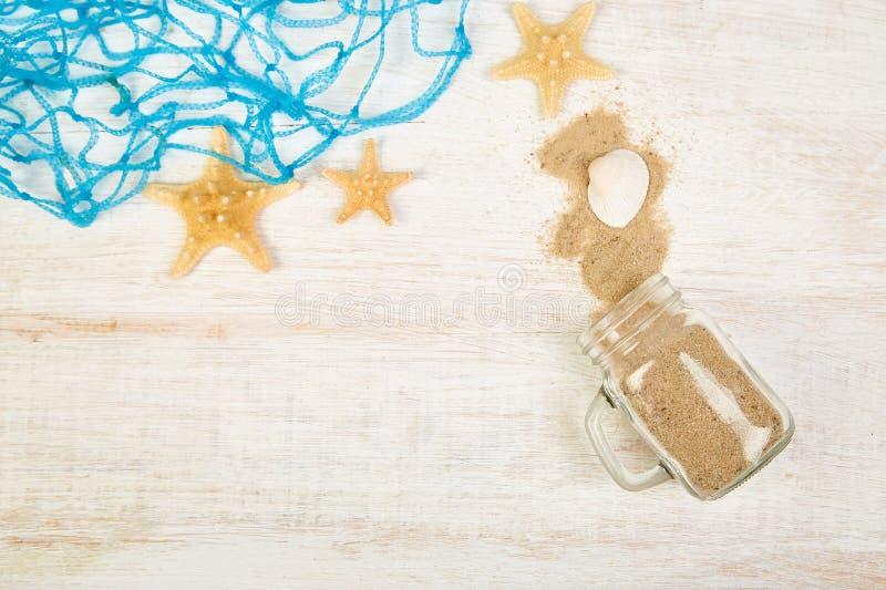 Starfish et coquillages, verre avec sable sur fond blanc image stock