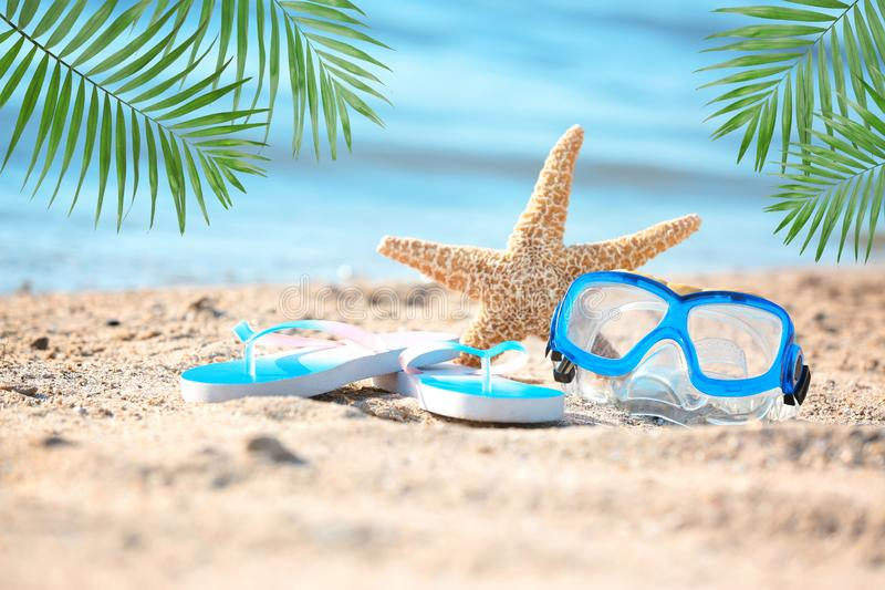 Starfish, goggles and flip flops on sand near sea. Beach object stock photo