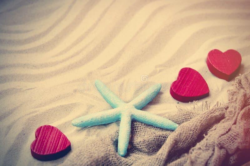 Starfish, Herzen und Fischnetz auf dem Sand lizenzfreie stockfotografie