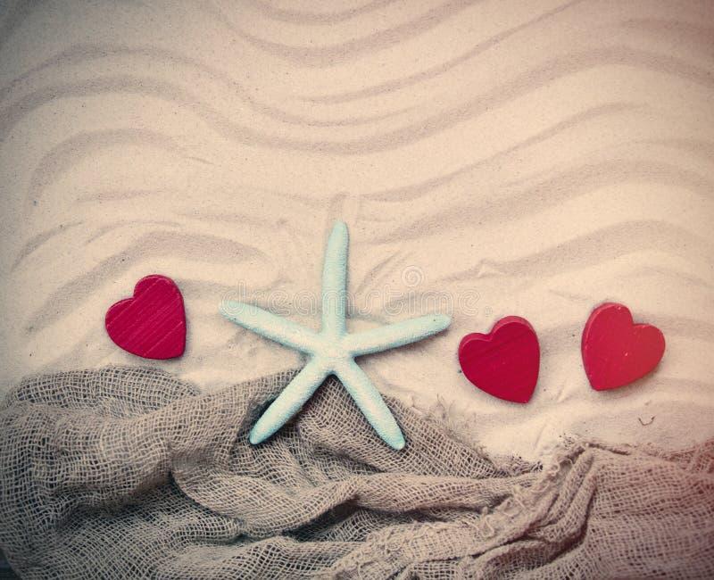 Starfish, Herzen und Fischnetz auf dem Sand lizenzfreie stockfotos