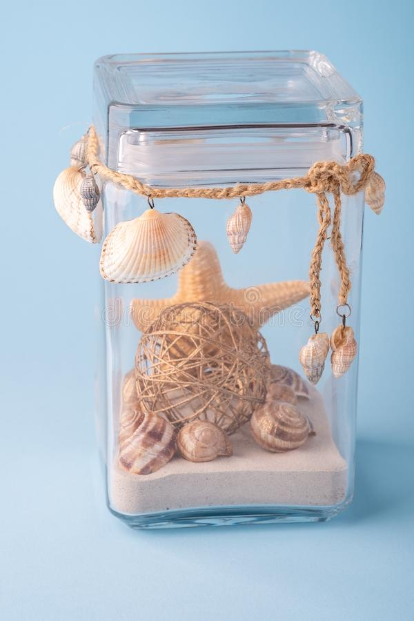 Starfish with seashell and sand in transparent glass jar  on blue background stock photo