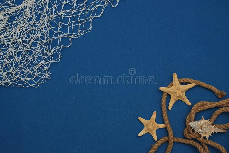 Starfish, Shell, Stones, Rope and Net Against a Blue Background with Copy Space. Summer Holliday. Nautical, Marrine concept. royalty free stock photography