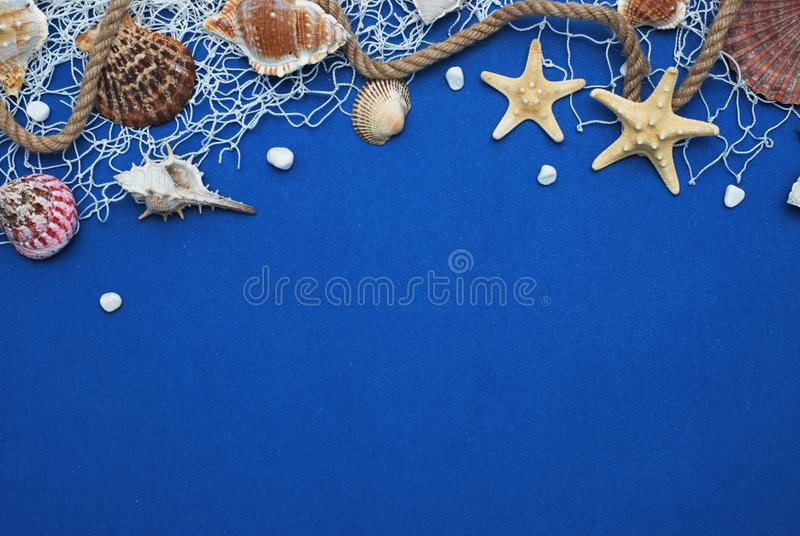 Starfish, Shell, Stones, Rope and Net Against a Blue Background with Copy Space. Summer Holliday. Nautical, Marrine concept. stock image