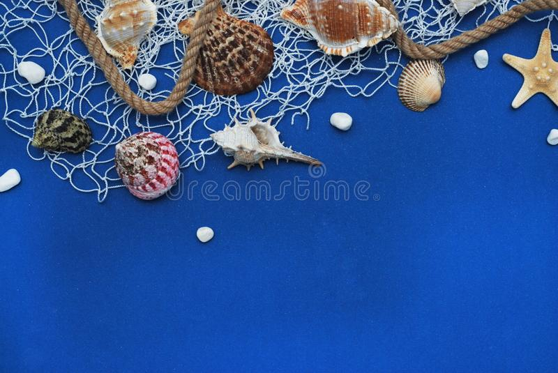 Starfish, Shell, Stones, Rope and Net Against a Blue Background with Copy Space. Summer Holliday. Nautical, Marrine concept. stock images