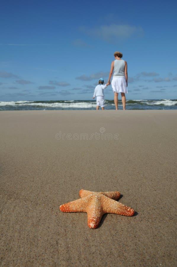 Starfish und Mutter mit Kind auf dem Strand stockbild