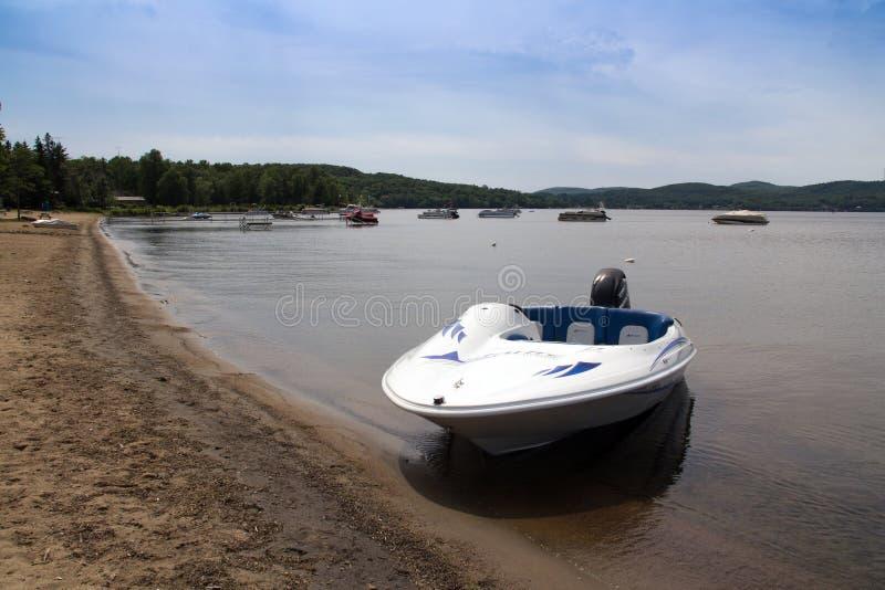 Starfresh fritids- fartyg med en kvicksilvermotor på en strand av Maskinongé sjön, Quebec, Kanada på sommardagen arkivfoton