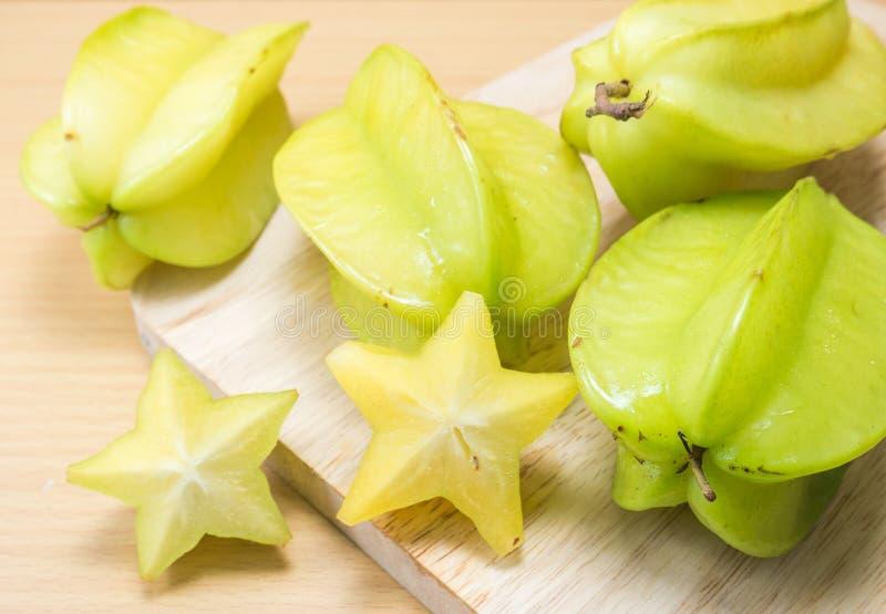 Starfruit och starfruitskiva på en wood bakgrund arkivfoto
