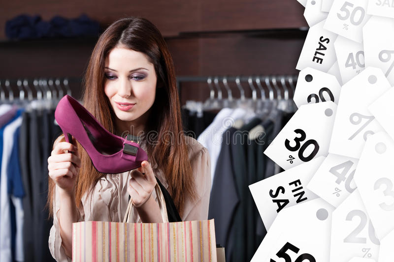 Staring at excellent shoes at the shopping center at a good price. Woman stares at excellent fuchsia shoes at shopping center at a good price stock images