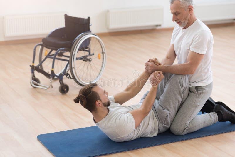 Stark åldrig ortoped som hjälper handikappade personer i idrottshallen arkivbilder