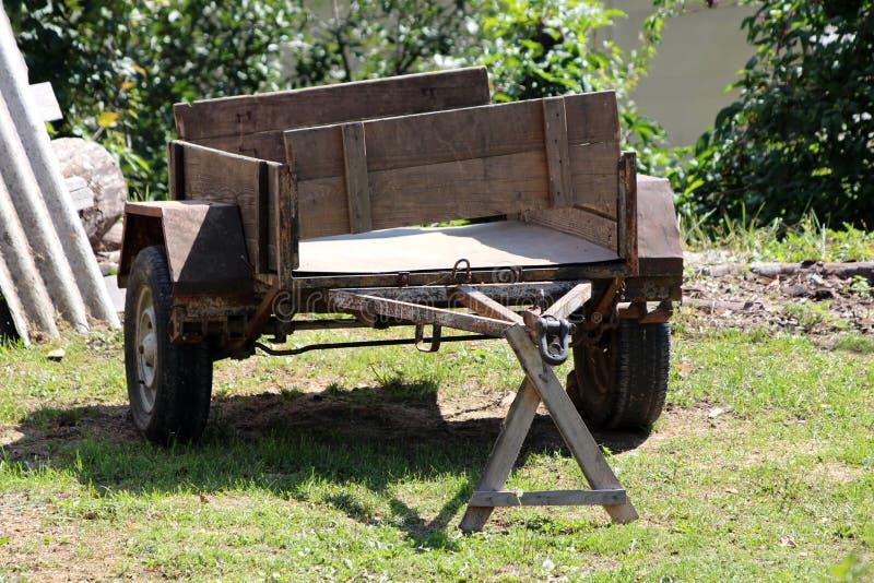 Stark beanspruchter alter Pkw-Anhänger mit verrostetem Metall und hölzerne Teile verließen auf Gras im Hinterhof, der mit Baumate stockfotografie