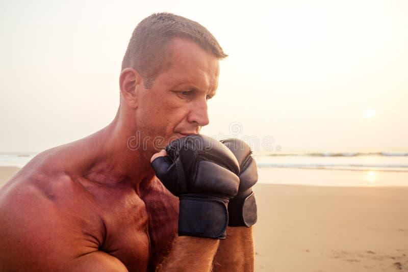Stark boxare som kämpar med träning på kickboxning med tränare vid solnedgång nära porträtt av en snygg fritids man royaltyfria bilder
