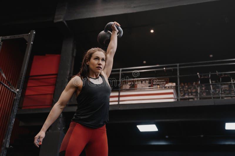 Stark crossfitkvinna som övar med en kettlebell på idrottshallen Kvinnlig görande funktionell utbildning fotografering för bildbyråer
