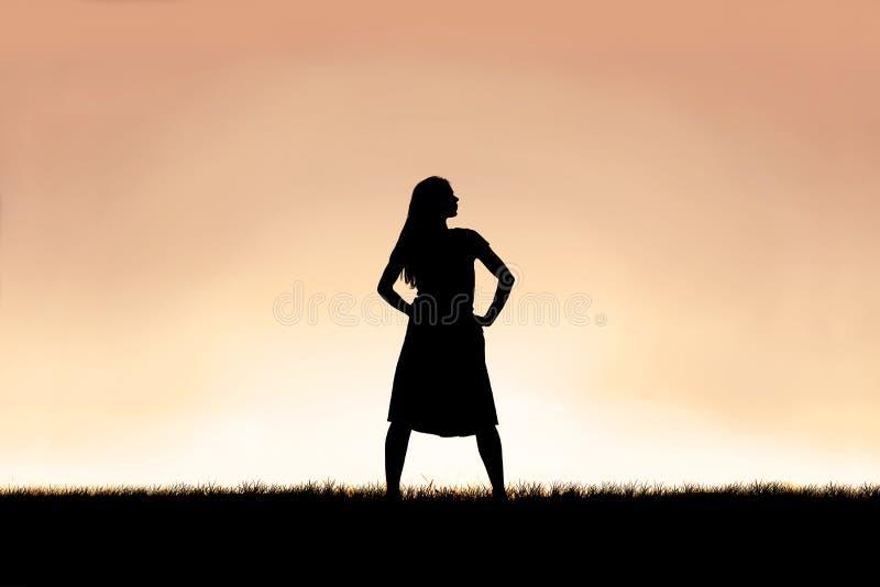 Stark härlig kvinnakontur som isoleras mot solnedgånghimmelbakgrund arkivbilder