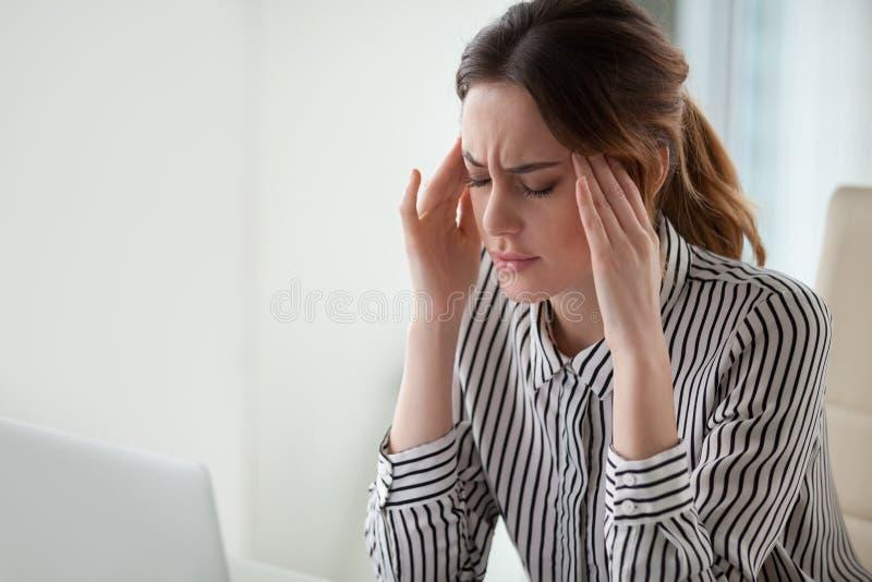 Stark huvudvärk för trött stressad affärskvinnakänsla som i regeringsställning masserar tempel arkivbilder