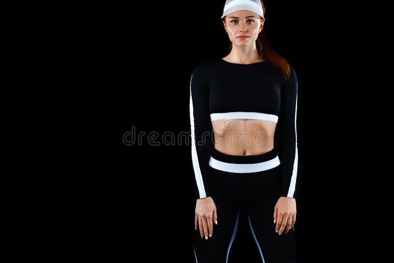 Stark idrotts- kvinna som poserar på svart bakgrund som bär i sportswear Energikondition och sportmotivation kopia arkivbilder