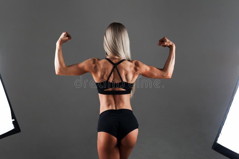 Stark idrotts- kvinnakonditionmodell som poserar tillbaka muskler, triceps, latissimus över svart bakgrund Mode- och glamourstil royaltyfri fotografi