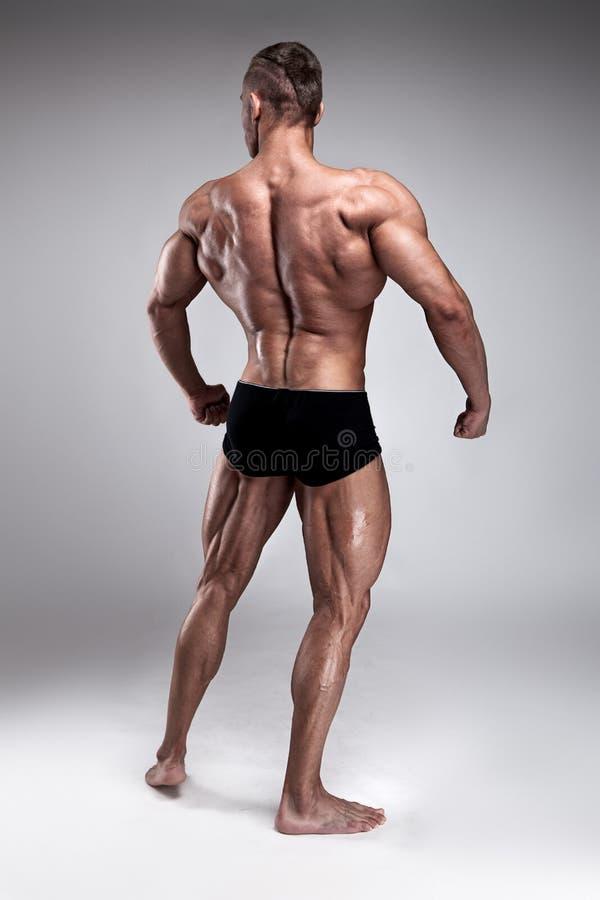Stark idrotts- mankonditionmodell som poserar tillbaka muskler arkivbild