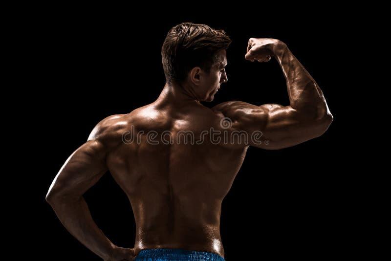 Stark idrotts- mankonditionmodell som poserar tillbaka muskler, triceps över svart bakgrund arkivbilder