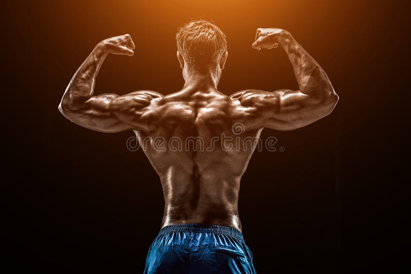 Stark idrotts- mankonditionmodell som poserar tillbaka muskler, tricepsnolla arkivfoto
