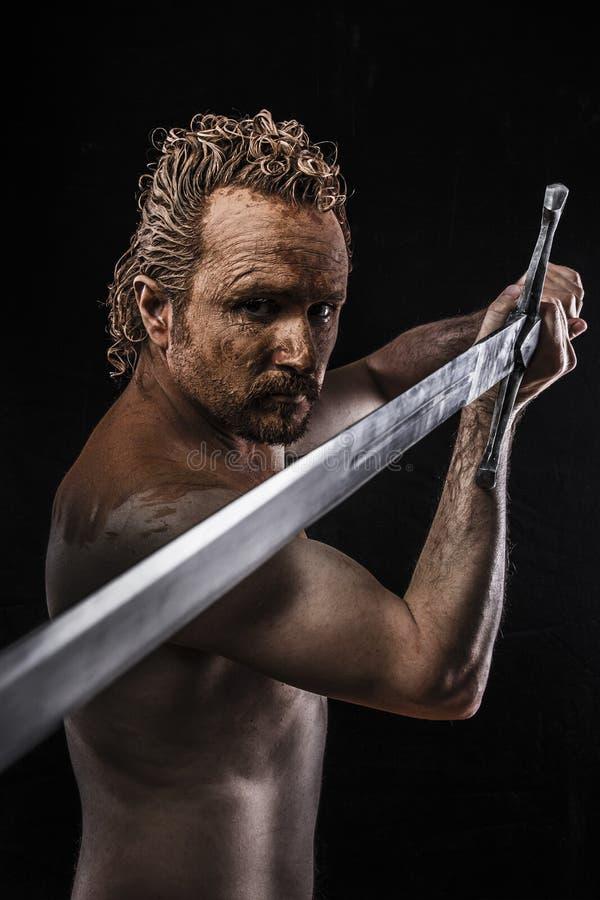 Stark krigare som slickar ett stort svärd som täckas i gyttja och som är naket arkivbild