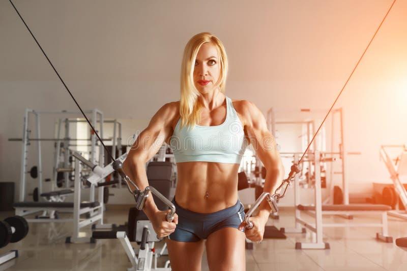 Stark kvinna som gör övning i idrottshallen royaltyfri foto