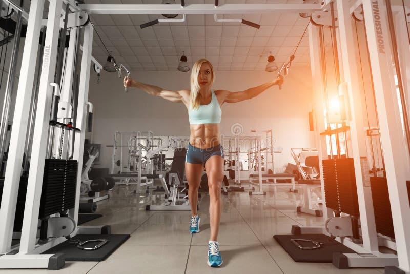 Stark kvinna som gör övning i idrottshallen royaltyfri bild