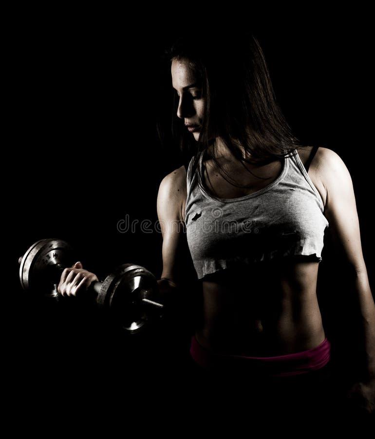 Stark kvinna som utarbetar med tunga vikter fotografering för bildbyråer