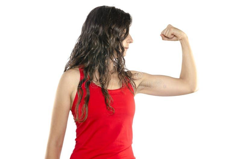 stark kvinna Ung kvinna som visar henne muscularity, medan isolerat royaltyfria foton