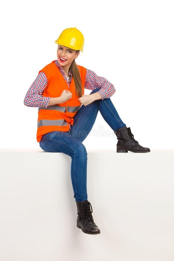 Stark kvinnlig byggnadsarbetare Sitting On en överkant royaltyfria foton