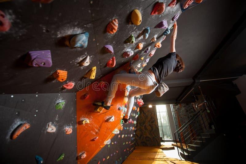 Stark kvinnlig klättrare på stenblockklättringväggen inomhus fotografering för bildbyråer