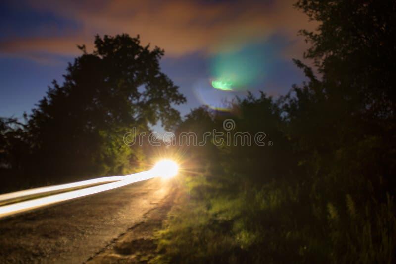 Stark ljus bilslinga på den suddiga gatan, lång exponering royaltyfria foton