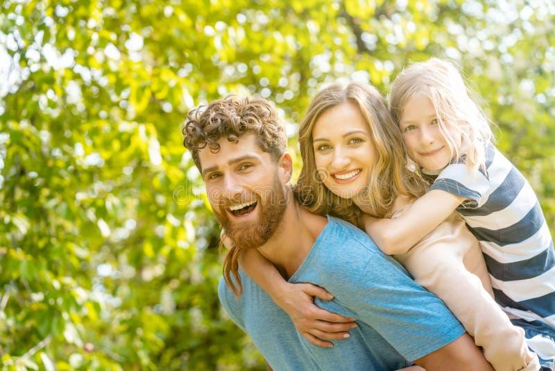 Stark man som stöttar hans familj, genom att bära fru- och dotterridtur på axlarna royaltyfri foto