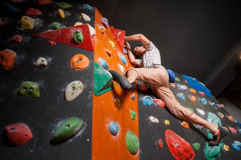 Stark manlig klättrare på stenblockklättringväggen inomhus royaltyfri fotografi