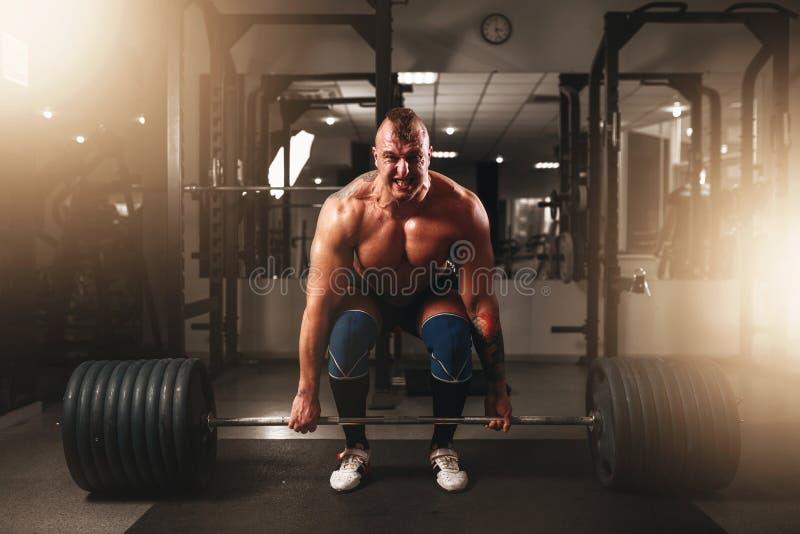 Stark manlig kroppsbyggare som lyfter vikten arkivfoto