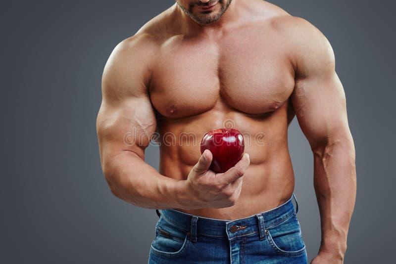 Stark muskelman som rymmer en röda Apple royaltyfri fotografi