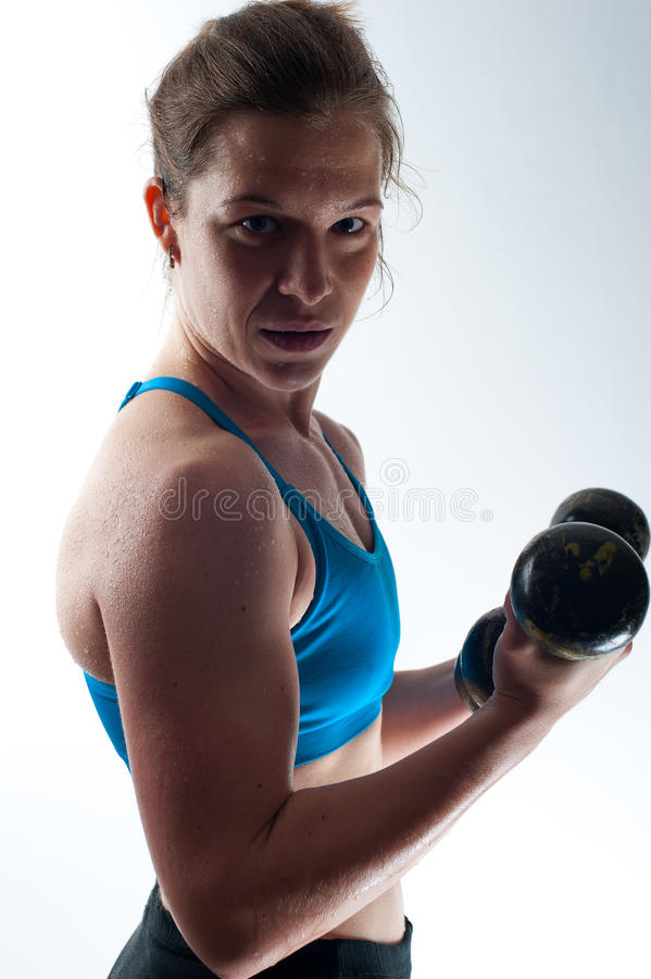 Stark muskulös kvinna som övar med hantlar arkivbild